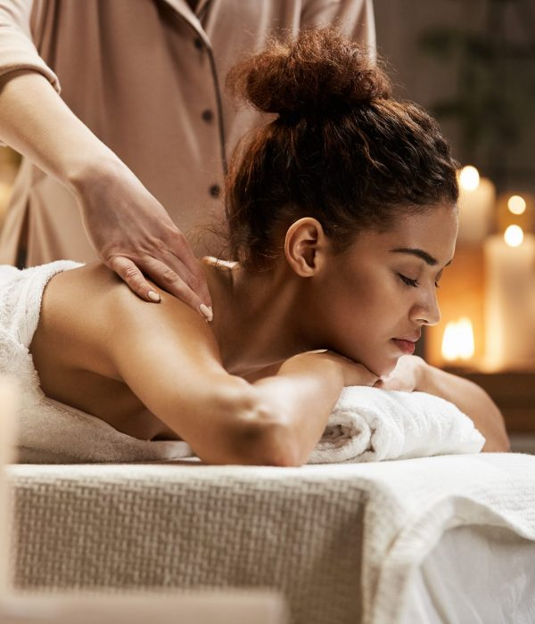 Young tender african girl smiling enjoying massage with closed eyes in spa resort.